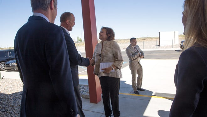 At far left, Taylor Lawrence, Raytheon Company vice-president and president of Missile Systems joins a greeting part y for New Mexico Gov. Susana Martinez on Friday at Raytheon Diné Facility south of Farmington.