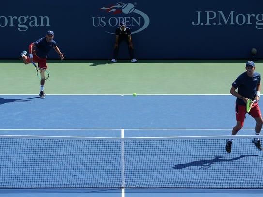 Mike Bryan hits a serve while Bob waits at the net