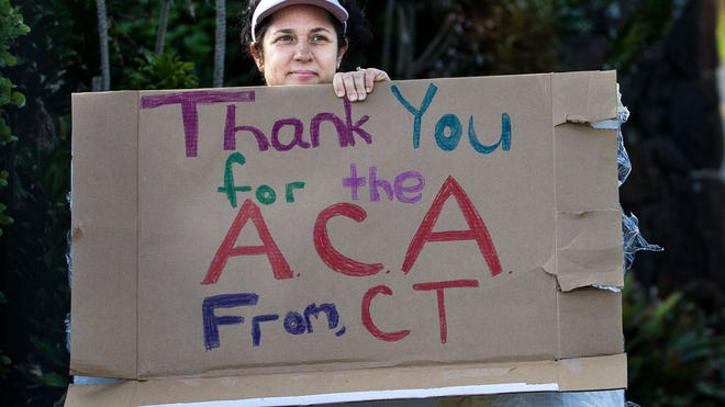 A woman holding a sign in support of the Affordable Care Act is seen as President Obama's motorcade returns to his vacation compound in Hawaii on Dec. 29.