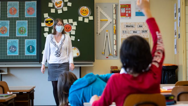 A teacher wearing protective face mask as she teaches close to pupils at a primary school in Morges, Switzerland, Monday, May 11, 2020. Swiss primary and secondary schools reopened with half of the students during the ongoing coronavirus Covid-19 pandemic.
