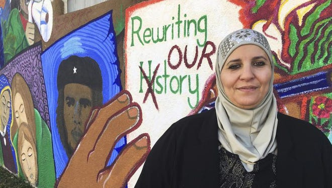 In this Wednesday, Feb, 1, 2017 photo, activist Samia Assed stands in front of a mural at the Albuquerque Center for Peace and Justice coalition in Albuquerque, N.M. Assed, a Palestinian-American, has now turned her fears over Donald Trump's election into action, joining what advocacy groups said are hundreds, possibly thousands of women of color, who are exploring making a run for public office.