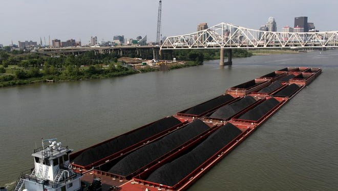 A barge carries coal through Louisville on the Ohio River in June 2013.