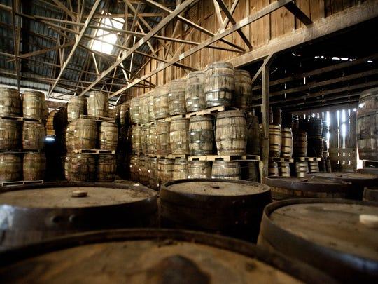 Oak barrels holding whiskey age in an old cow barn
