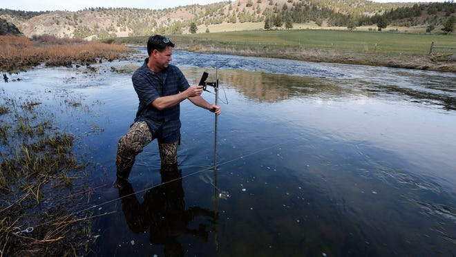 Jeremy Giffin, Deschutes Basin watermaster, measures the current last month in the Crooked River near Prineville Reservoir in Central Oregon. The reservoir, which was only about 83 percent full, is fed in part by snowmelt. However, snowpack was light this year, which has contributed to drought conditions in much of the state.
