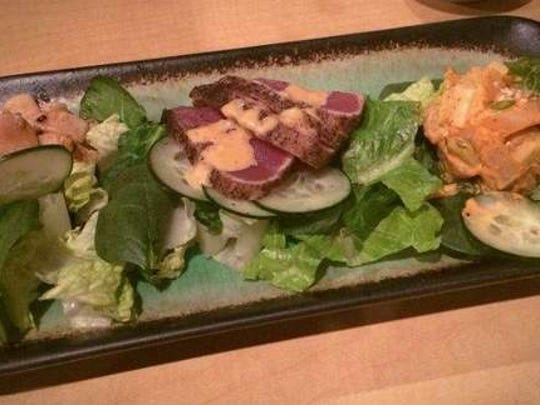 The Tataki Trio ($14), sickle pomfret served in a spicy salad, seared ahi tuna and broiled unicorn fish, is served on a bed of lettuce and cucumbers at Kyodai in North Liberty.