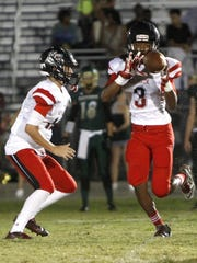 South Fort Myers QB Michael Morris tosses a high hand-off to Ke'Shon Murray at the Island Coast-South Fort Myers football game Friday in Cape Coral.