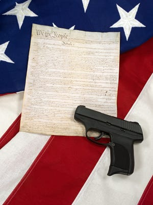 Copy of US Constitution with hand gun on American flag background. Concept of second amendment rights.