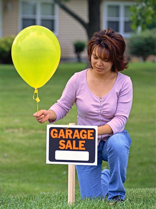 A woman tying a balloon on garage sale sign