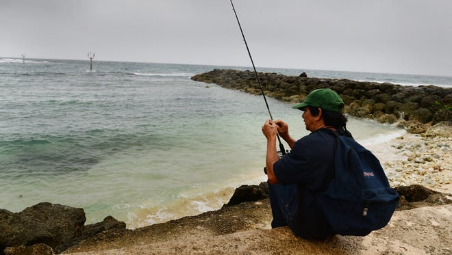 "Jess Guerrero, of Dededo, prepares to drop a line in the churning seas of the HagŒt–a boat basin area on July 12, 2014, hoping to catch imperial fish or skipjack. ""Fish tend to move when (the sea) is rough,"" he said. Pacific Daily News file photo 