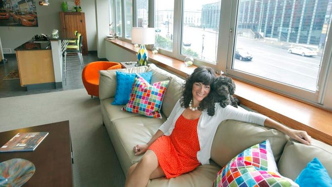 Robin Plummer and her Maltipoo, Delilah, relax in the 1,150-square-foot loft at 44 Exchange Blvd. she shares with her husband, Ron. They sold a much larger,  historic home in  Le Roy to move to downtown Rochester. Their rent is $1,200 a month.
