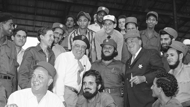 FILE - In this March 21, 1959, file photo, a Cuban baseball fan, center,  wears Los Angeles Dodgers' owner Walter O'Malley's cap while O'Malley sports a rebel's hat and a sheriff's badge during an exhibition baseball game between the Dodgers and Cincinnati Redlegs in Havana, Cuba. At left center, Dodgers director Bud Holman grins wearing an army captain's beret.  Reds' general manager Gabe Paul, seated at lower left, also tries out a rebel officer's hat. Others are unidentified. The game would be the last between major league teams in Cuba for the next four decades. (AP Photo/File)