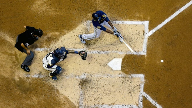 Milwaukee Brewers' Lorenzo Cain hits a single during an intrasquad game July 14 at Miller Park in Milwaukee. Home plate as a coronavirus transmission hot spot is just once concern as an abbreviated season gets underway.