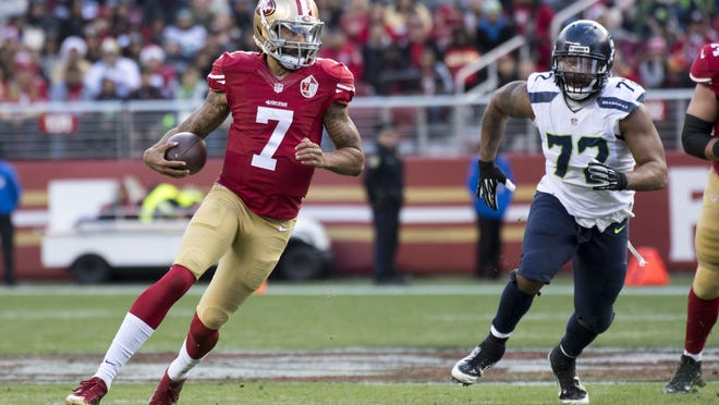 49ers quarterback Colin Kaepernick runs the ball against Seahawks defensive end Michael Bennett during a game Jan. 1, 2017.