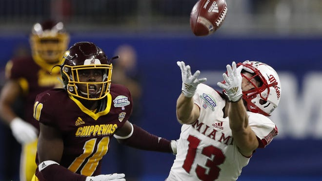 In this Dec. 7, 2019, file photo, Miami of Ohio wide receiver Jack Sorenson (13) attempts to catch a pass as Central Michigan defensive lineman LaQuan Johnson (11) defends during the first half of the Mid-American Conference championship NCAA college football game in Detroit. The Mid-American Conference announced Friday, Sept. 25, 2020, that it will have a 6-game football season, meaning all 10 major conferences will play this fall.
