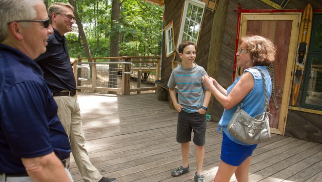 """From left, David Weber, Doug Armstrong, CEO of North Star Reach Camp, 14-year-old Dominic Weber and mom Patti talk Tuesday, June 13, 2017 at a tour of the tree house in which Dominic was featured as part of an episode of the DIY Network television show """"The Treehouse Guys."""""""