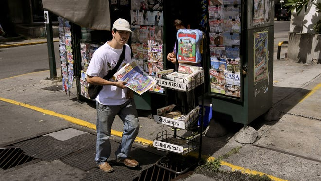 9/3/2013 _ Caracas, Venezuela _ A man purchases a newspaper at one of the many kiosks in Caracas.  A paper shortage may result in some newspaper closings.  Photo by Girish Gupta for USA TODAY [Via MerlinFTP Drop]