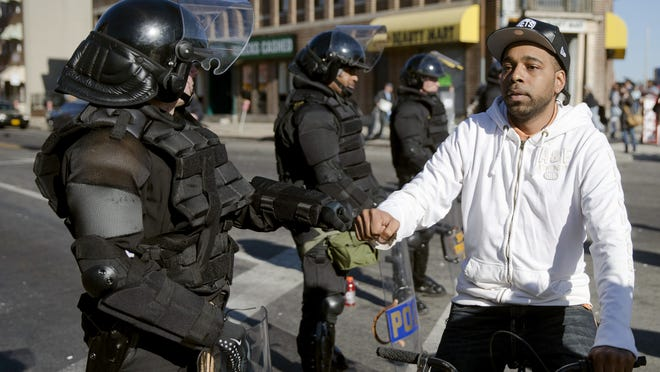 A man on a bicycle greets Maryland State Troopers Tuesday, April 28, 2015, in the aftermath of rioting following Monday's funeral for Freddie Gray, who died in police custody. The violence that started in West Baltimore on Monday afternoon had spread to East Baltimore and neighborhoods close to downtown and near Camden Yards. The New Jersey State Police are sending 150 personnel to Maryland to assist. (AP Photo/Matt Rourke)