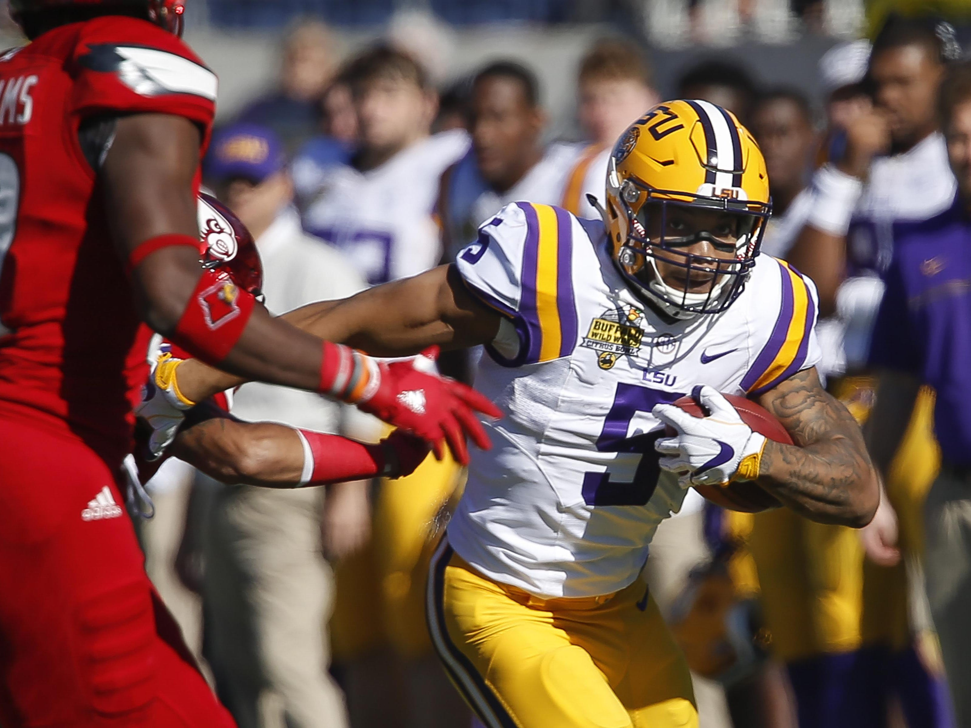LSU Tigers running back Derrius Guice (5) runs for a first down during the first quarter of an NCAA football game against the LSU Tigers in the Buffalo Wild Wings Citrus Bowl at Camping World Stadium.