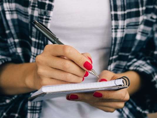 Woman in plaid shirt and a red manicure pen writing