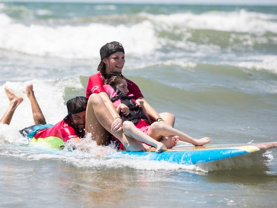 """Volunteers help Lucia Martinez of San Antonio surf during """"They Will Surf Again"""" event at Horace Caldwell Pier in Port Aransas on Saturday, June 10, 2017."""