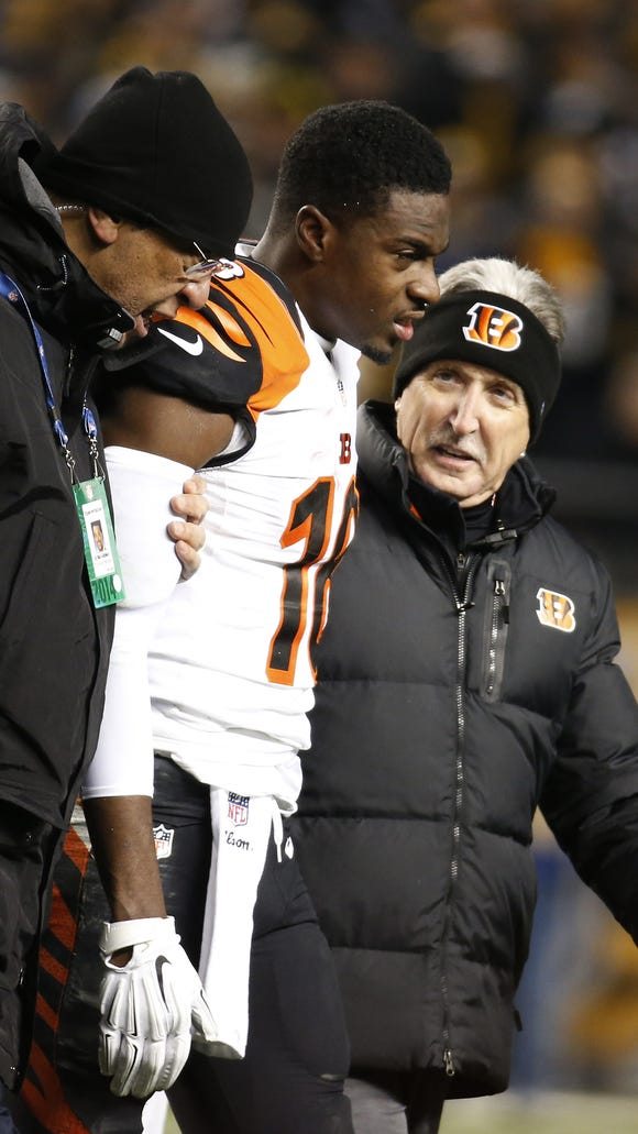 Cincinnati Bengals wide receiver A.J. Green (18) is helped off the field after taking a hit.