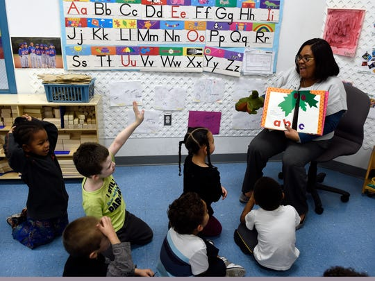 Deiona Clayton reads a book to her Pre-K students at