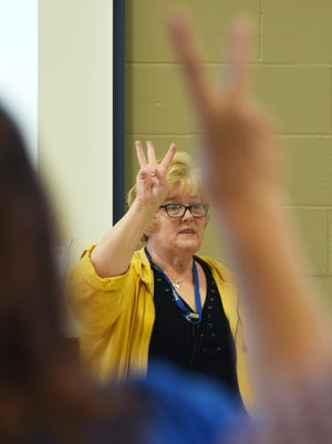 Instructor Lois Frame signs a letter at a sign language class at Starlight School on Thursday.