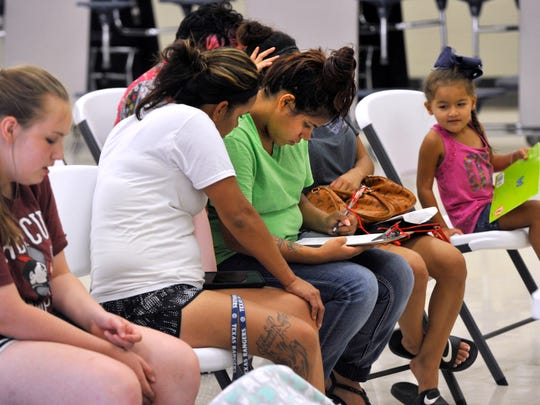 Monique Carrillo (in green) fills out registration forms for her son at Long Early Learning Center Wednesday July 26, 2017.