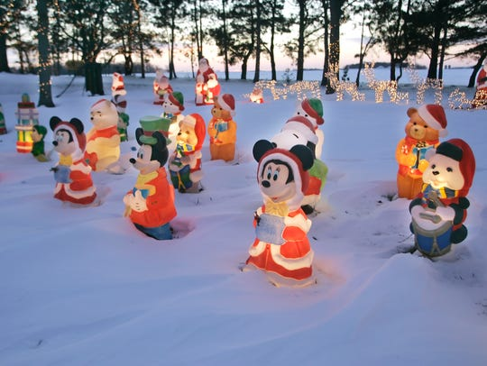 A wide variety of Christmas figures covers a yard at
