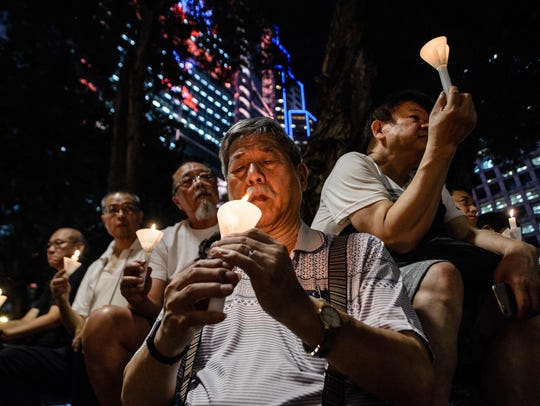 People hold candles as they attend a vigil in Hong