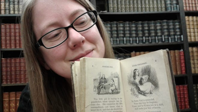 Colleen Theisen displays a very readable example of one of the larger books in the miniature collection, an 1864 illustrated edition of children's devotions that was likely a Sunday school gift. This book is about 4 inches tall.