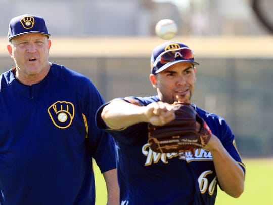Brewers bench coach Pat Murphy looks on as pitcher Hiram Burgos looks to home plate, during spring training drills in Phoenix.