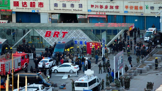 Security personnel inspect the explosion site outside Urumqi South Railway Station in northwest China's Xinjiang Uygur Autonomous Region, April 30, 2014, after a deadly explosion.