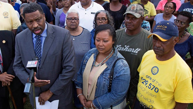 Derrick Johnson, left, president of the Mississippi NAACP, center left, talks to the media on behalf of Stacey Payton, center right, and Hollis Payton, behind his wife Stacey, in front of the Stone County Courthouse in Wiggins, Miss., Monday, Oct. 24, 2016.