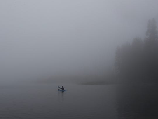 David Yu,16 paddles across Manzanita Lake in Lassen Volcanic National Park as fog blanketed the area on Monday.