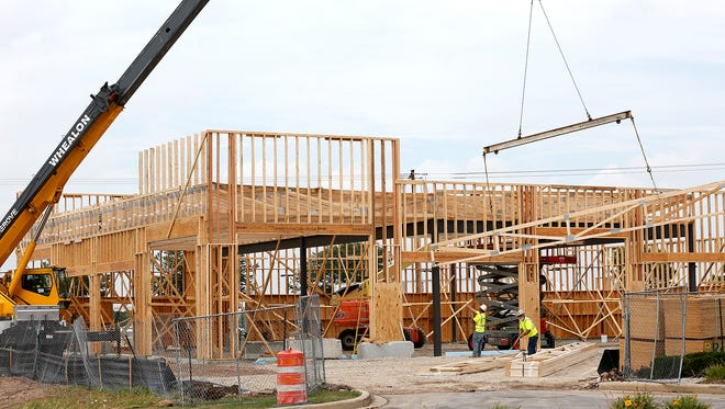 Construction workers build what will be a three-unit strip mall on the south east corner of Johnson Street and Rolling Meadows Drive.