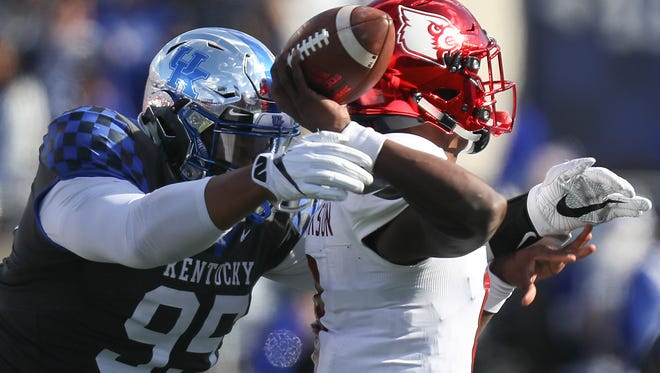 Lamar Jackson is hit by Kentucky's Quinton Bohanna in the first half.