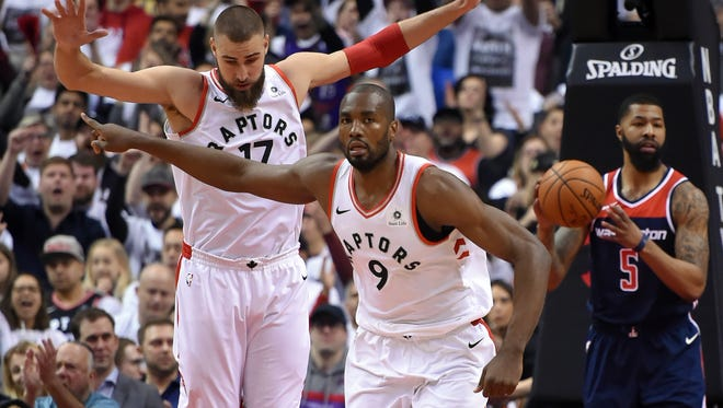 Toronto Raptors forward Serge Ibaka (9) and center Jonas Valanciunas (17) react after scoring against Washington Wizards in game one of the first round of the 2018 NBA Playoffs at Air Canada Centre.