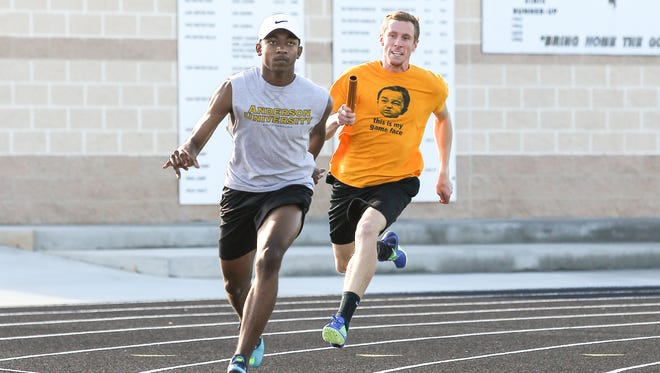 Caleb Stephenson, right, of Anderson University practices a handoff with teammate Jordan Anderson, left, with his team practicing at T.L. Hanna High School in Anderson. Stephenson runs in the 100 meters, 200 meters, 400 meters, 400 meters hurdles, 4 x 100 meters relay, and 4 x 400 meters relay for the Trojans.