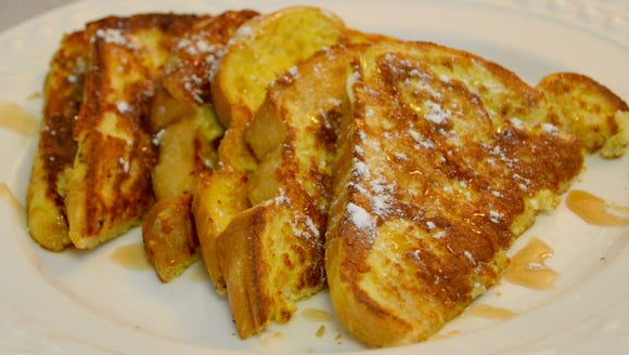 French toast drizzled in syrup and powdered sugar.
