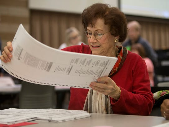 A woman moves a pile of ballots during the recount