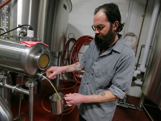 Jason Asch of Asbury Park, head brewer, sample checks