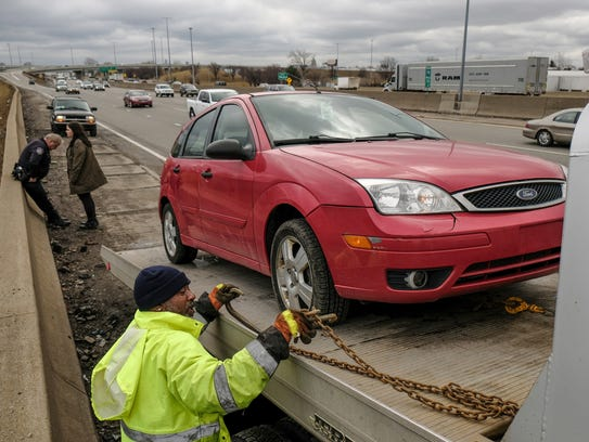 United Towing worker Devon Gayle loads a car belonging to Emily Tujaka, left, of Grosse Pointe after getting a flat tire from hitting a pothole heading northbound on I-75 near the McNichols Road exit in Detroit on Wednesday, February 21, 2018. Tujaka said she seen more than 20 cars pulled over around her after hitting the potholes as she waited for AAA to get a tow truck to her. Tujaka had been waiting for nearly six hours before her car was loaded.