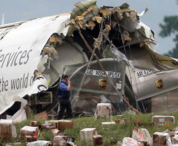 A postal officer inspects the debris at the scene of a United Parcel Service cargo plane crash near Birmingham-Shuttlesworth International Airport on Aug. 14 in Birmingham, Ala. Two crew members were killed when the aircraft crashed on a hill at 5 a.m. near the airport.