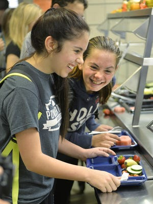 Foley High School ninth-grader Ashlee Miller, left, shares a laugh with a friend as they pick up fruits and vegetables Tuesday in the school's lunch line. The school participates in the Farm to School program that incorporates locally grown fruits and vegetables into school lunch menus.