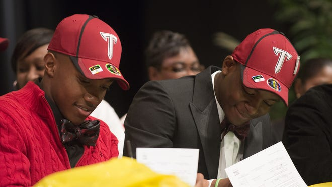 ALBERT CESARE/ADVERTISER G.W. Carver football players Melvin Tyus, right, and Ismail Saleem sign with Troy. Carver football players Melvin Tyus, right, and Ismail Saleem sign with Troy University on Wednesday, Feb. 4, 2015, at Carver High School in Montgomery, Ala.
