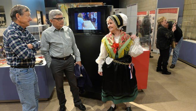 """Dressed in traditional Slovenian costume, Cindy Gauthier, Minneapolis, talks to her brother, Wayne Anderson, left, of Plymouth, and friend John Medved on Sunday, Oct. 16, 2016, at the new Stearns History Museum Slovenian heritage exhibit titled """"Farmers, Miners, and Refugees: Slovenian Immigration in Minnesota Since 1855."""""""
