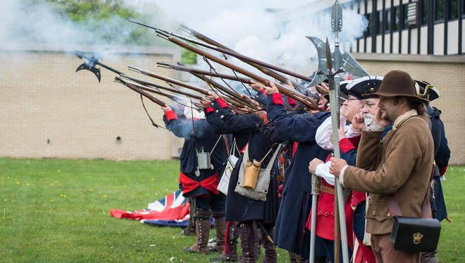 Members of the Massachusetts Provincial Battalion fire their rifles during the opening ceremony of the Feast of the Ste. Claire Saturday, May 26, 2018 at Pine Grove Park in Port Huron.