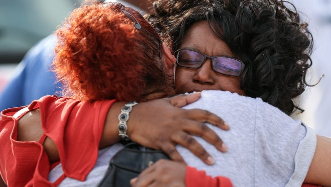 From right, Renee Bacon hugs Yvonne Vergara during a prayer vigil at the Shell gas station at 34th Street and Sherman Drive, where 50-year-old Sheriff Jallow was fatally shot the previous day, on the east side of Indianapolis, Wednesday, May 30, 2018.