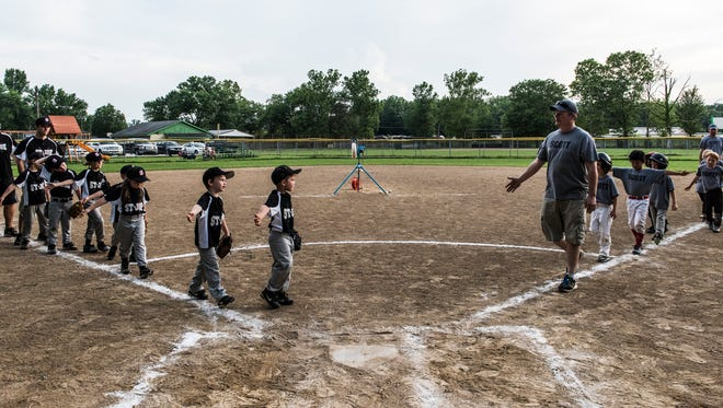 The St. Joe (left) and Scott (right) youth baseball teams line up to high-five one another at the end of the game held at the Scott Township baseball fields in June 2017.